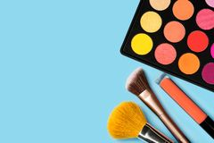 Black plastic palette of brightly coloured yellow, red, pink, orange eyeshadow, orange liquid lipgloss, and two make-up brushes. Arranged in the corner of royalty free stock photos