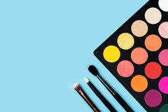Black plastic palette of brightly coloured yellow, red, pink, orange eyeshadow and three make-up brushes of various types arranged. In the corner of pastel baby royalty free stock photography