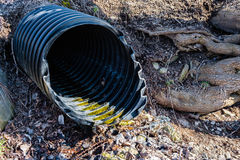Black plastic pipe emerging from ground. Royalty Free Stock Photos