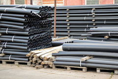 Black plastic pipes. Manufacture of plastic pipes Stock Photos