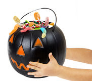 Black plastic pumpkin filled with candy, hand of kid Royalty Free Stock Images