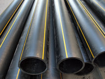 Black plastic PVC pipes on the street Stock Photos