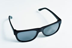 Black plastic rimmed sunglasses. Closeup of a pair of black plastic rimmed sunglasses on an off-white surface Stock Images