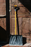 Black plastic snow shovel with orange handle at the wooden door royalty free stock photos