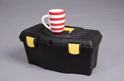 A Black plastic toolbox and a drinking mug Stock Photos