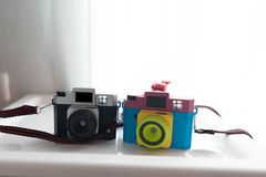 Black plastic toy camera and blurred mix color cameraon shelf ne royalty free stock image