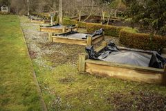 Black plastic weed prevention on raised planting beds. Black plastic is applied to raised planting beds after early spring cleanout to prevent emerging weeds Royalty Free Stock Photo