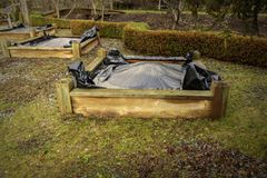 Black plastic weed prevention on raised planting beds. Black plastic is applied to raised planting beds after early spring cleanout to prevent emerging weeds Stock Photos