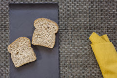 Black plate with bread and yellow napkin on warp background Stock Image