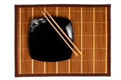 Black plate with chopsticks. Japananese style plate on bamboo rug Stock Image