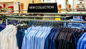Black plate in a clothing store with a sign NEW COLLECTION. Black plate above new shirts and pants in blue white burgundy colors what hung on hangers in big shop Stock Photography