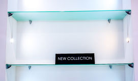 Black plate in a clothing store with a sign NEW COLLECTION. White shop wall with glass shelve and black plate. medium tringle black plate in a clothing store Royalty Free Stock Images
