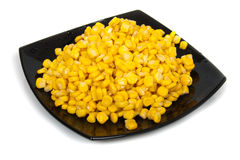 Black plate with corn seeds Royalty Free Stock Photography