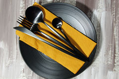 A black plate with cutlery Stock Photos
