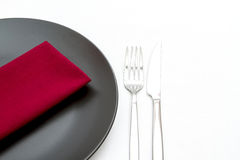 Black plate with cutlery and napkin Stock Photo