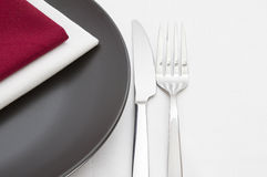 Black plate with cutlery with napkins Royalty Free Stock Photography
