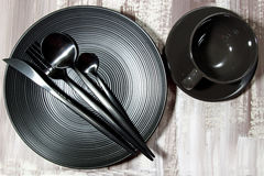 A black plate with cutlery Stock Image