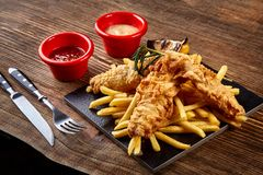 Black plate with fish and chips, mayo and ketchup on wooden background. Still life. Copy space Royalty Free Stock Image