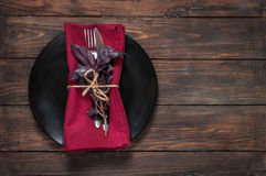Black plate with fork,knife, napkin and basil on wooden table Royalty Free Stock Image