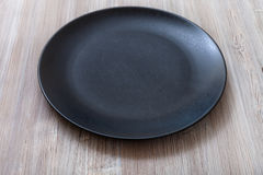 Black plate on gray brown table Royalty Free Stock Image