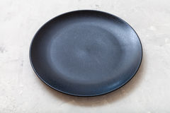 Black plate on gray concrete surface. One black plate on gray concrete surface Royalty Free Stock Photo