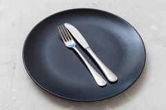 Black plate with parallel knife, spoon on concrete Royalty Free Stock Image