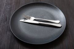 Black plate with parallel knife, spoon on dark Stock Photo