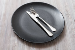 Black plate with parallel knife, spoon on gray Royalty Free Stock Photos