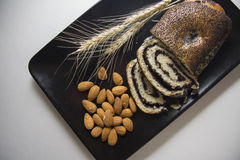 Black plate with poppy strudel and almonds royalty free stock images