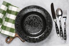 Black plate, silverware and kitchen napkin Royalty Free Stock Photo