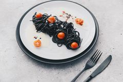 Plate of black spaghetti with tomatoes cherry Royalty Free Stock Images