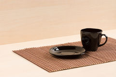 Black plate standing near black tea cup on tablemat. Royalty Free Stock Photo