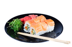 Black plate with sushi and chopsticks Stock Images