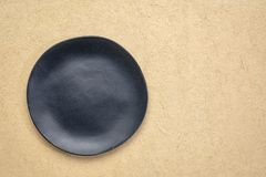Black plate on textured paper royalty free stock photos