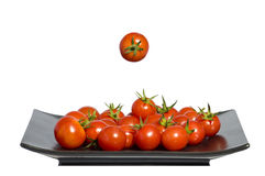 Black plate tomatoes, floating tomatoe, copy space Royalty Free Stock Image