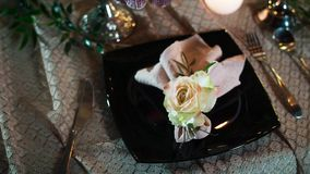 A black plate on which lies a decorative flower and a napkin, left and right cutlery, lies on the tablecloth on the. Table, handheld stock footage