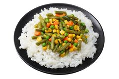 Black plate with white rice, green peas, canned corn kernels, cut green beans isolated on white background royalty free stock photography