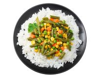 Black plate with white rice, green peas, canned corn kernels, cut green beans isolated on white background. top view royalty free stock photography