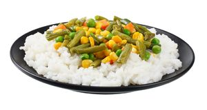 Black plate with white rice, green peas, canned corn kernels, cut green beans isolated on white background royalty free stock images