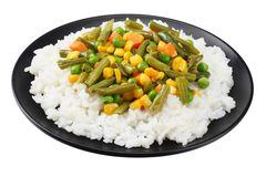 Black plate with white rice, green peas, canned corn kernels, cut green beans isolated on white background stock image