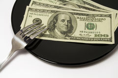 Black plate whith money. Bank eat my money. Black plate whith money Royalty Free Stock Photography