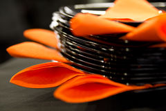 Black plates. And orange napkins photographed with small depth of field Royalty Free Stock Images