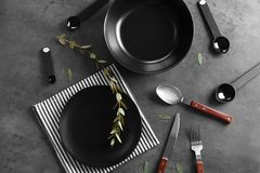 Black plates and cutlery on gray background. Top view stock image