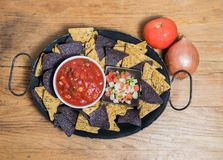 Chips, salsa and pico de gallo in a black platter royalty free stock image