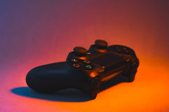 Black Playstation 4 controller. Cumbria, UK - December 21, 2016: Black Playstation 4 game controller lit with dynamic coloured lighting Royalty Free Stock Image