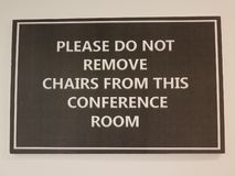 Black please do not remove chairs from the conference room sign. On white wall stock photo