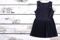 Black pleated classic dress for schoolgirl. Classic signature school girl sleeveless dress and copy space. Cute cotton girl dress for school wear Stock Photography