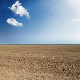 black agriculture field and blue sky with clouds Stock Image