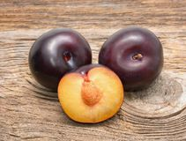 Black plums isolated on wooden background Royalty Free Stock Photos