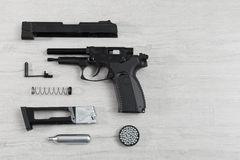 Black pneumatic pistol (air gun) gun unassembled on a lighten ba Royalty Free Stock Images